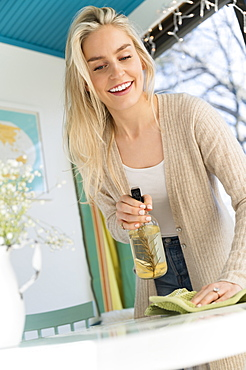 Smiling woman cleaning tabletop with natural cleaning spray