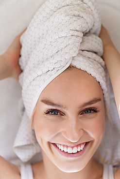 Portrait of smiling woman with head wrapped in towel