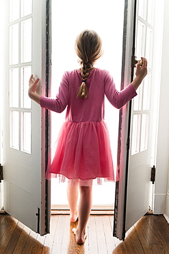 Rear view of girl (6-7) walking through doorway into light
