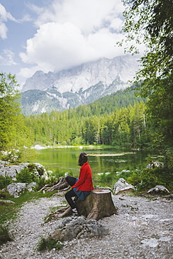 Germany, Bavaria, Eibsee, Woman sitting by Frillensee lake
