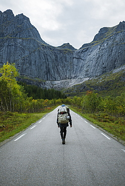 Norway, Lofoten Islands, Backpacker walking down road in mountain landscape
