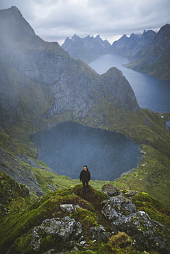 Norway, Lofoten Islands, Reine, Man on Reinebringen mountain with lake and fjord in background