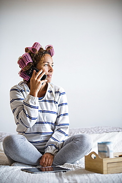 Woman with hair curlers sitting on bed and talking on mobile phone