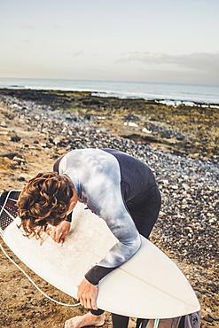 Teenage boy waxing surfboard at beach