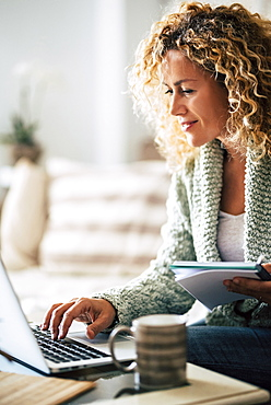 Smiling woman working with laptop on sofa