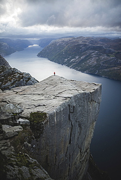 Person standing on Preikestolen cliff in Rogaland, Norway