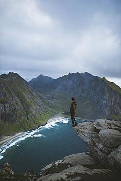 Man standing on cliff at Ryten mountain in Lofoten Islands, Norway