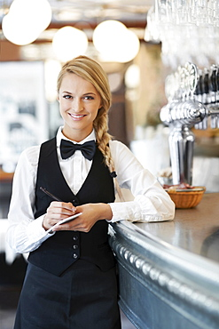 Portrait of smiling waitress standing by bar counter