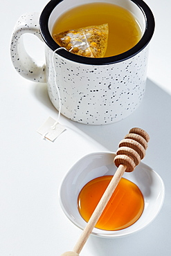 Cup of tea, honey dipper and bowl of honey