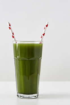 Green juice in cup with straws