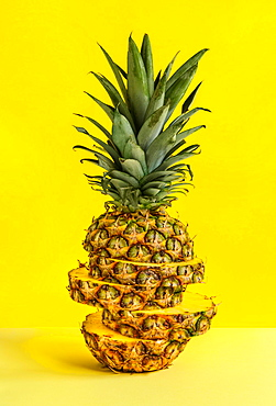 Sliced pineapple against yellow background