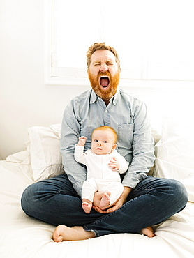 Yawning father sitting on bed with baby boy (2-3 months)