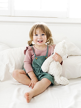 Girl (2-3) sitting on bed with teddy bear
