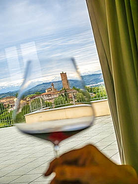 Italy, Barbaresco, Hand holding glass with barbaresco wine