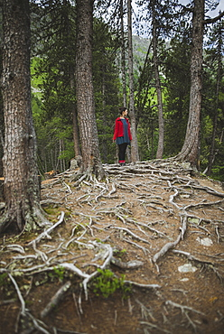 Switzerland, Bravuogn, Palpuognasee, Young woman standing in forest