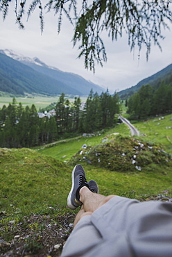 Switzerland, Obergoms, Legs of man relaxing on grass in Swiss Alps