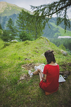 Switzerland, Obergoms, Young woman painting with watercolor in Swiss Alps