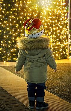 Boy in Christmas hat watching illuminated Christmas tree