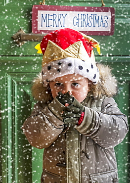 Boy wearing parka and Christmas hat during snowfall in front of green door