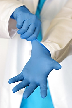 Person putting on blue surgical gloves