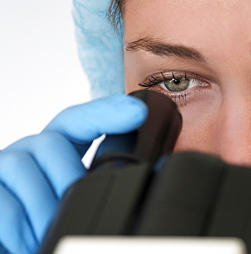Laboratory technician looking through microscope