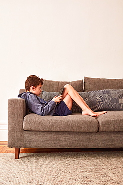 Boy (8-9) using tablet on sofa