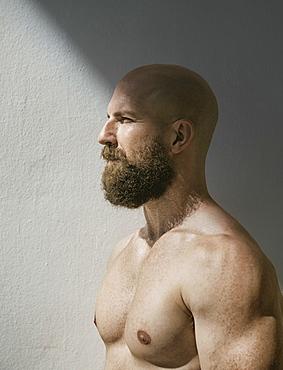 Profile of bald muscular man