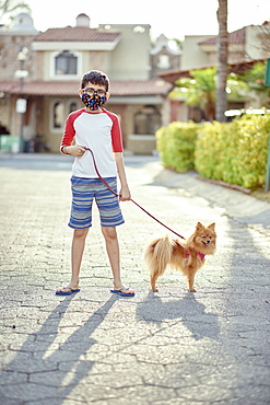 Mexico, Zapopan, Boy with face mask walking dog
