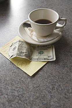 Sill life of cup of coffee money and check