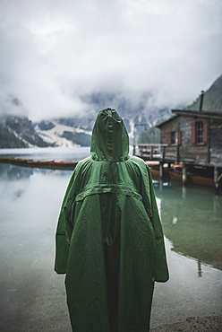 Italy, Man in raincoat standing Pragser Wildsee