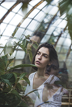 Ukraine, Crimea, Young woman looking at plant in greenhouse