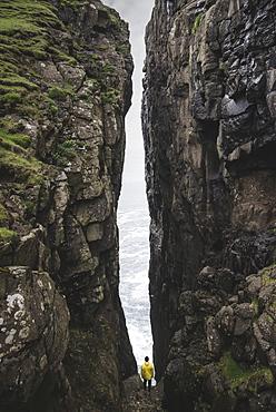Denmark, Faroe Islands, Sorvagur, Man standing between two cliffs