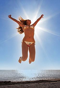 USA, Florida, Miami Beach, Young woman jumping on beach