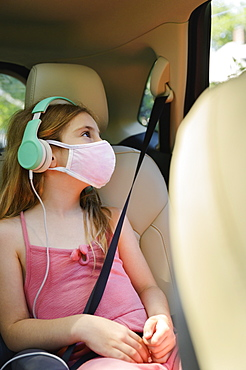 Masked girl (6-7) listening to music in car