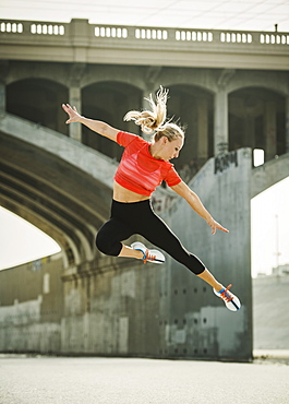 USA, California, Los Angeles, Sporty woman jumping in urban setting
