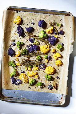 Roasted cauliflower with rosemary and olive oil on parchment paper
