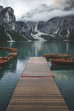 Italy, Pragser Wildsee, Dolomites, South Tyrol, Rowboats moored near jetty in mountain lake
