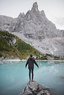 Italy, South Tyrol, Cortina d Ampezzo, lake Sorapis, Man standing on rock looking at lake