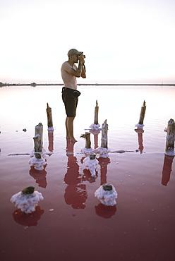 Ukraine, Crimea, Man standing in salt lake and taking photos