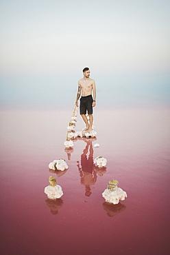 Ukraine, Crimea, Man standing on salt crystal in salt lake