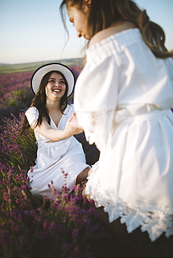 France, Young women in white dresses in lavender field