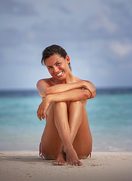 Maldives, Portrait of smiling woman sitting on beach
