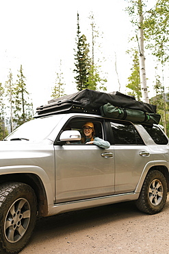 Woman sitting in off road car with tent on roof