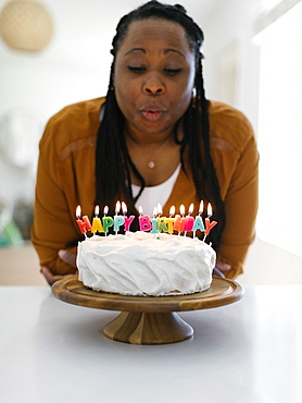 Woman blowing candles on birthday cake - 1178-30499