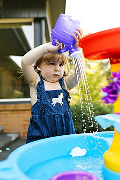 Toddler girl (2-3) playing with water in garden