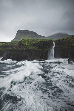 Denmark, Faroe Islands, Gasadalur Village, Mulafossur Waterfall, Coastline with Mulafossur Waterfall falling into Atlantic Ocean in stormy day