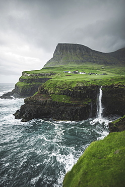 Denmark, Faroe Islands, Gasadalur Village,Mulafossur Waterfall, Coastline with Mulafossur Waterfall falling into Atlantic Ocean