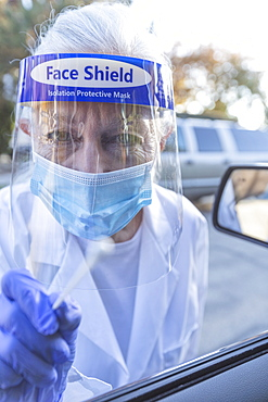 Female medical staff in protective clothing approaching car with coronavirus swab test