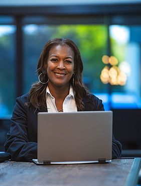 Portrait of smiling businesswoman sitting at desk with laptop in office