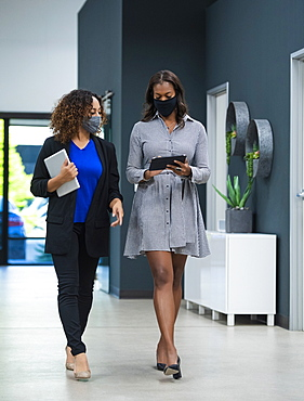 Businesswomen in face masks walking in office